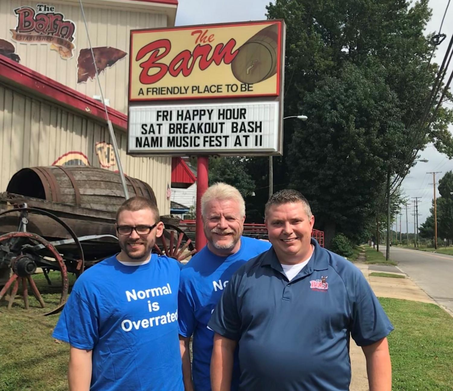 Anthony Hannan (left), Paul Quinn (middle) and Jim Watson (left) pose in front of The Barn sign that advertises the Breakout Bash happening Saturday. Photo provided by Paul Quinn before the 2018 Breakout Bash.