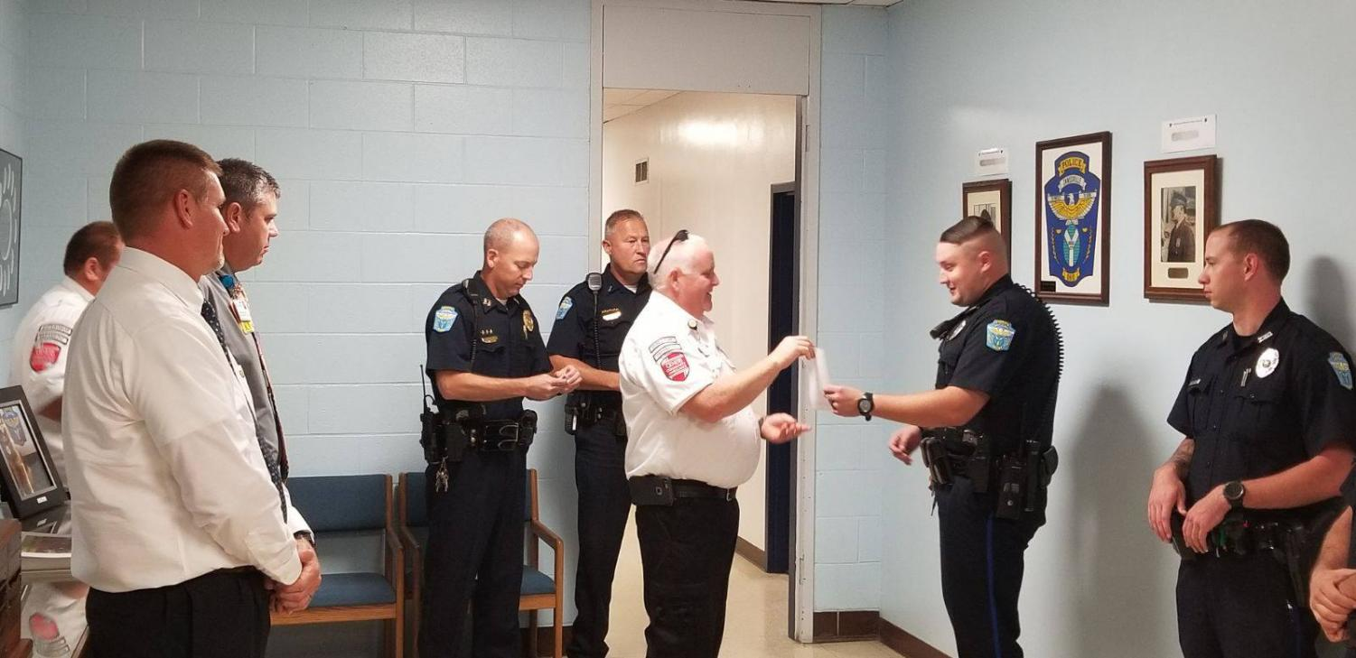 Patrolman Jeremy Downing is presented with The Life Saving Award surrounded by other ZPD officers. Photo provided by the Zanesville Police Department.