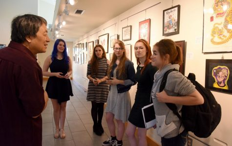 Professor Yan Sun asks Daphne Woodmansee of John Glenn High School about her background in art while talking to a group of artists from John Glenn.