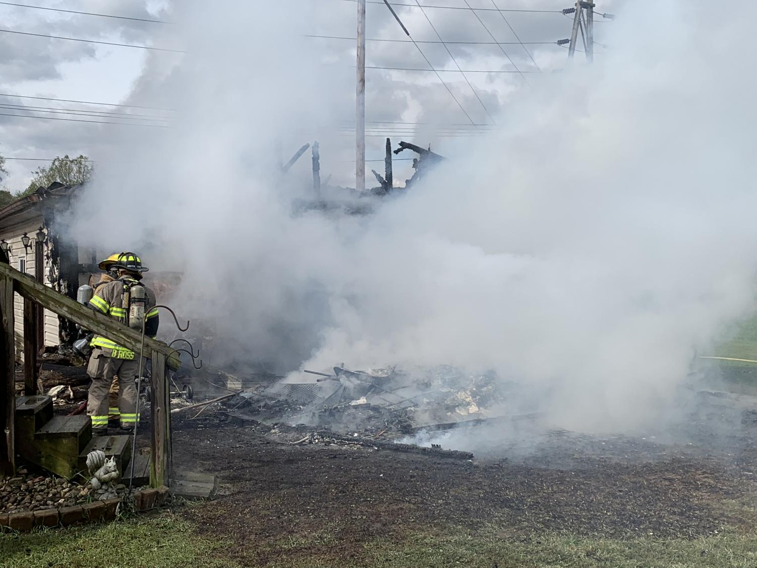 Firefighters work to extinguish the flames from a detached garage fire at the intersection of Elm Street and 3rd Street.