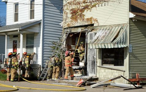 Firefighters breakdown the damaged front wall of the former Kimble's Meat Market Wednesday afternoon.