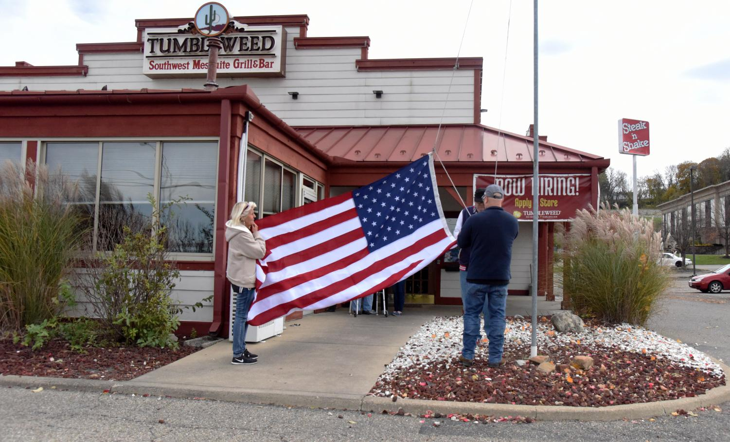 Members from the Carr Center unfold and raise the new America Flag up the flagpole outside of the Tumbleweed restaurant Wednesday, Nov. 7.
