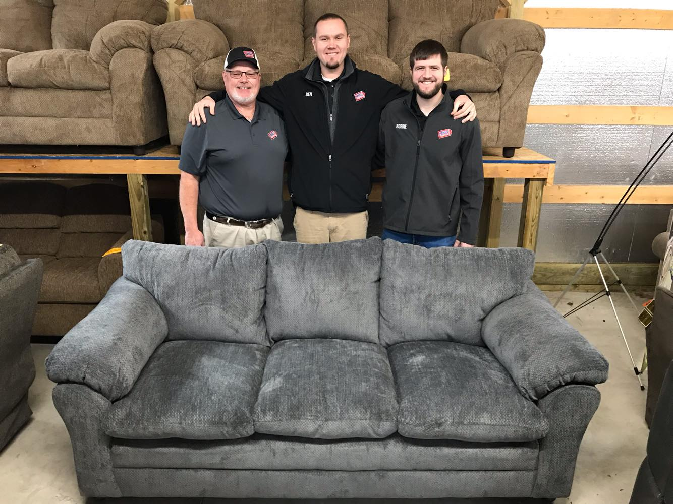 Paul Lowe (left), Big Ben Lowe (center) and Robbie Hisey (right) stand behind the beautiful new sofa Lowe's Bargain Barn Furniture is giving away to thank their customers during the holiday season.