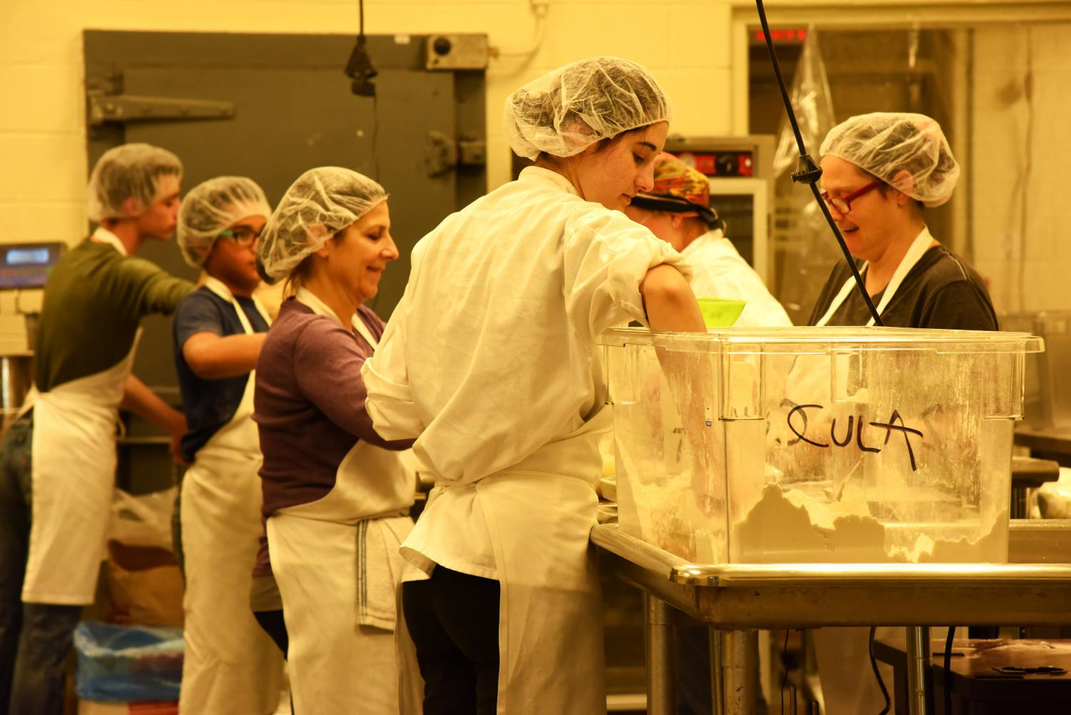 A crew of six, including Cecilia Ciarlo (middle left) pack the baking mix bags in the Foodworks Alliance kitchen on Nov. 30.
