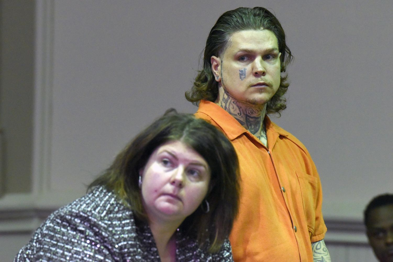 John Hampton (back) stands in court with his defense attorney Kendra Kinney (front).