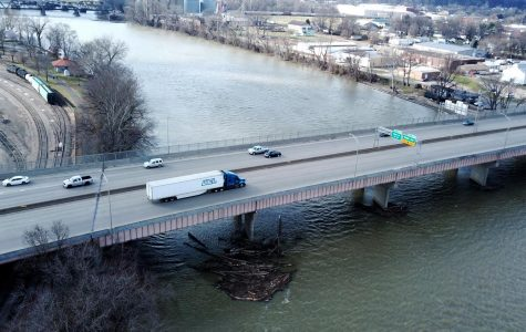 A cluster of logs has collected in the Muskingum river under the I-70 overpass.