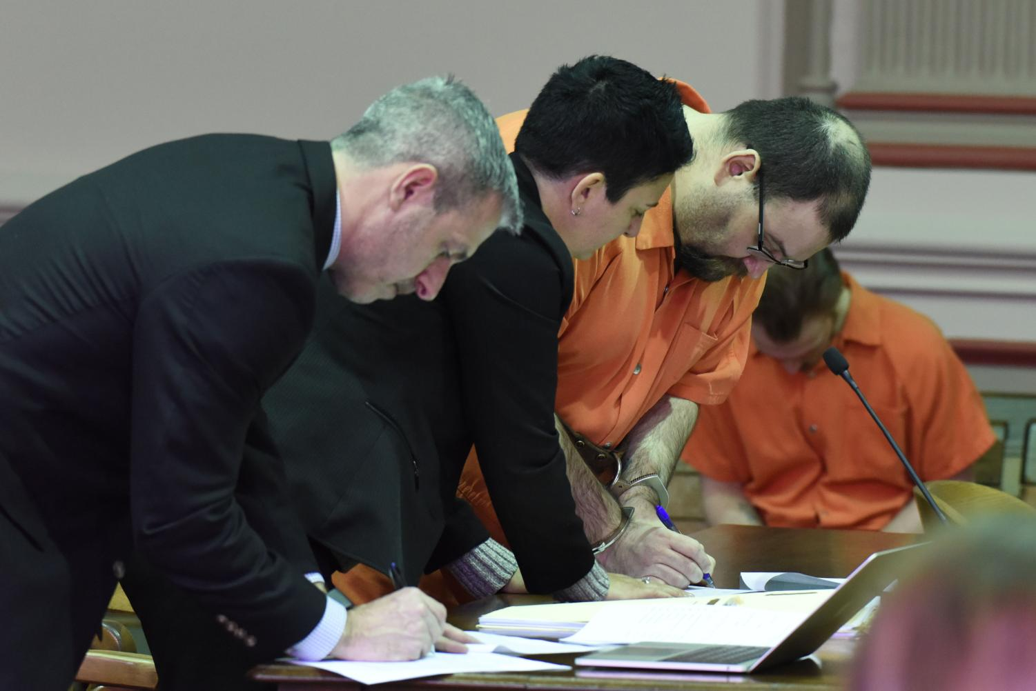 Matthew Stickdorn, his defense attorney Nicole Churchill and assistant prosecutor Ron Welch sign a amended plea form.