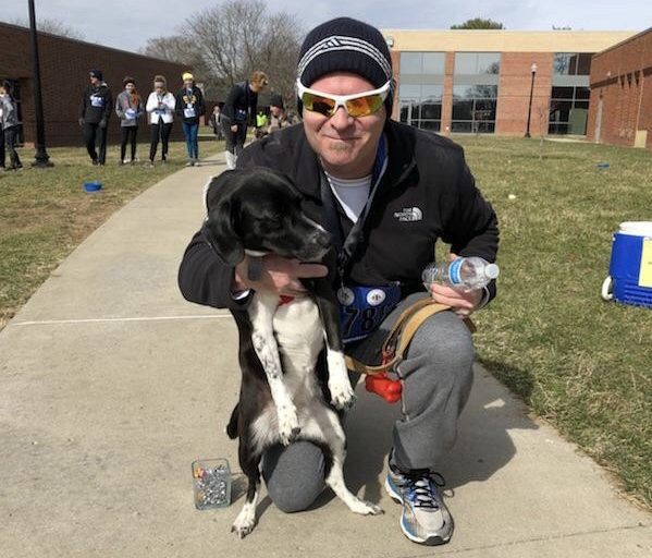 Dr. Lori Wahl's husband poses with one of their three dogs after finishing second in his category during the 2018 Dog N' Jog. | Photo provided by Dr. Lori Wahl.