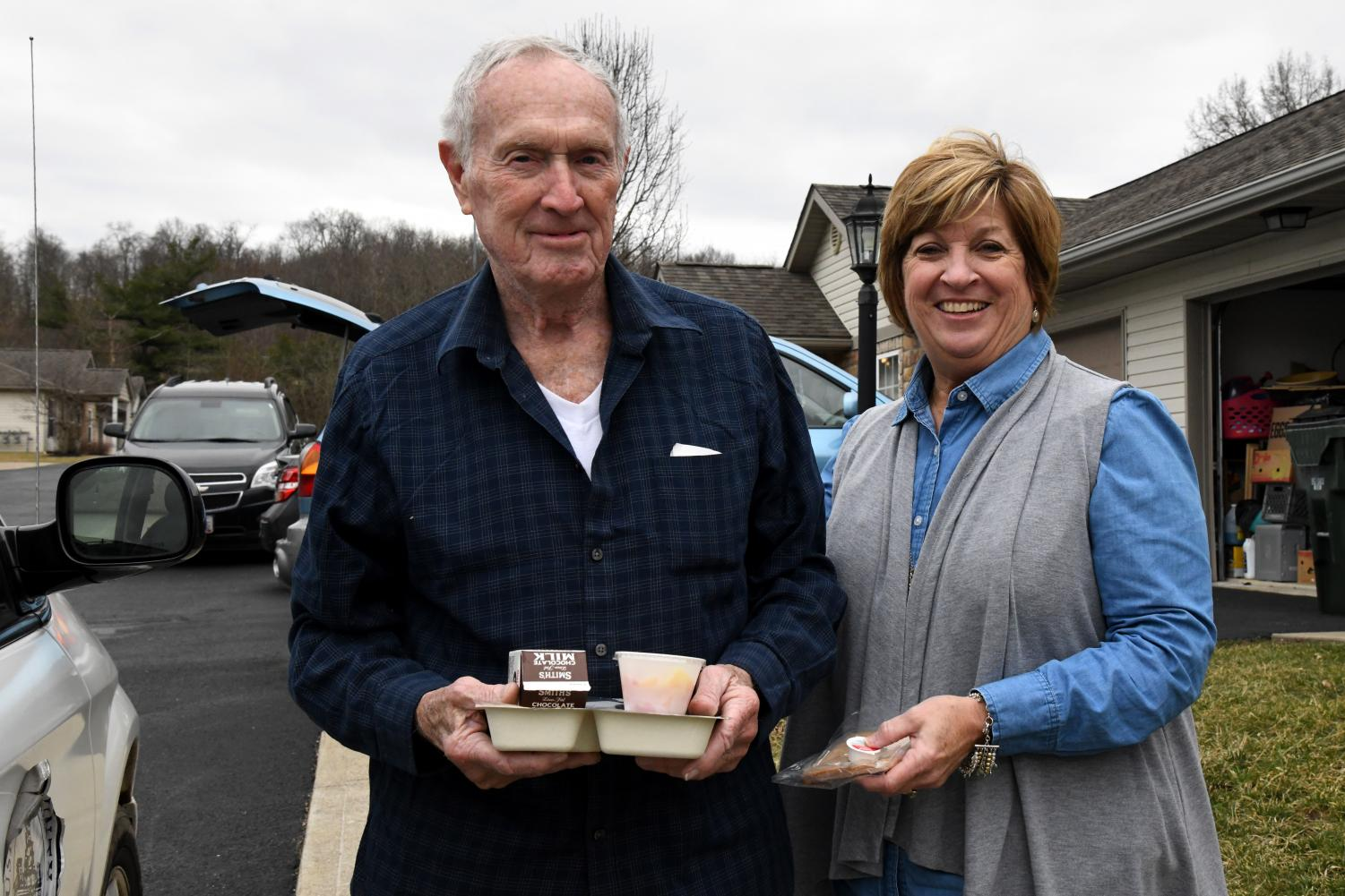 Muskingum County Commissioner Cindy Cameron (right) gives senior citizen William Hill (left) his daily meal during Friday's March for Meals initiative.