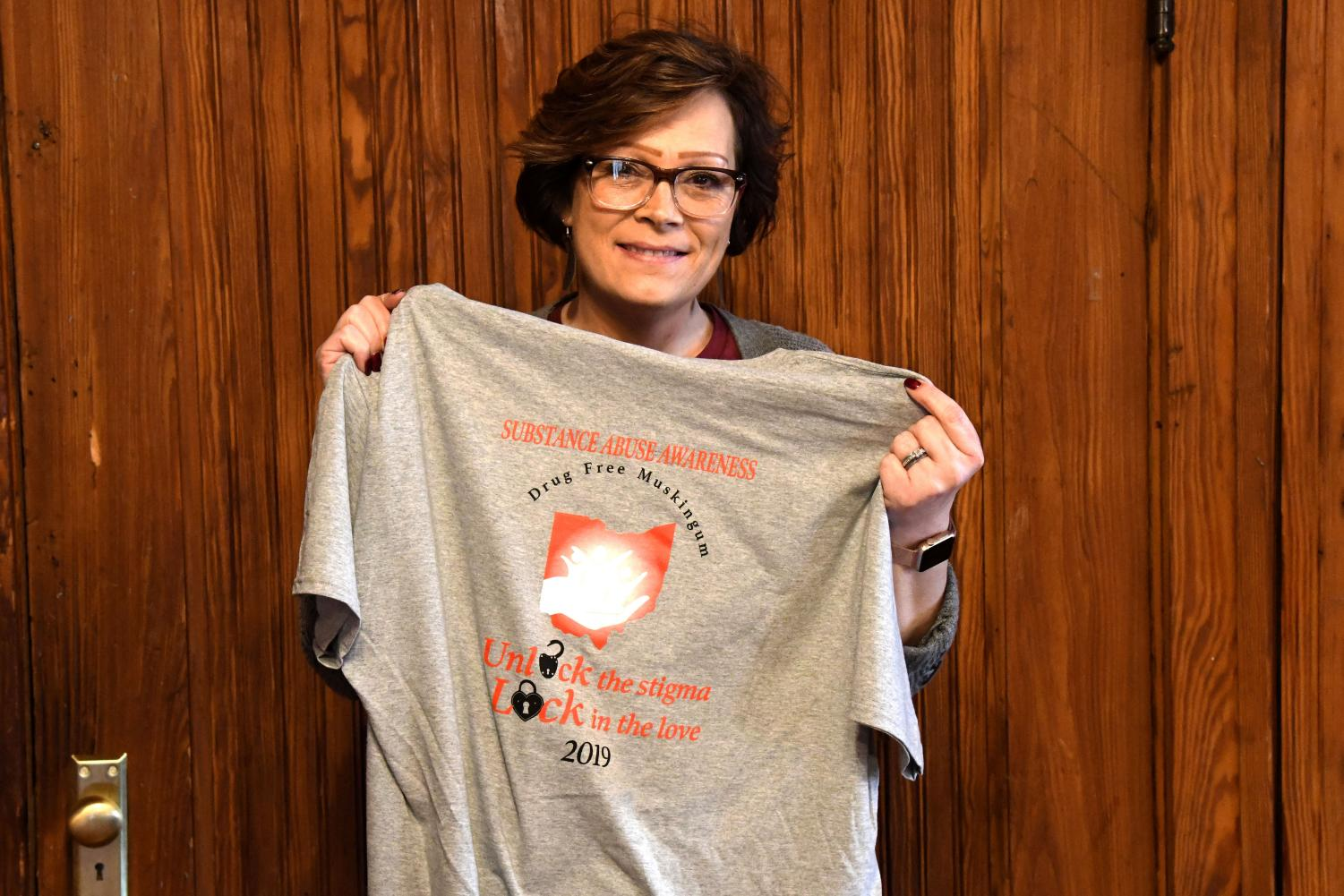 Monica Batteiger, one of the founders of Drug Free Muskingum, holds one of the organization's T-shirts for the Celebration of Life Walk.