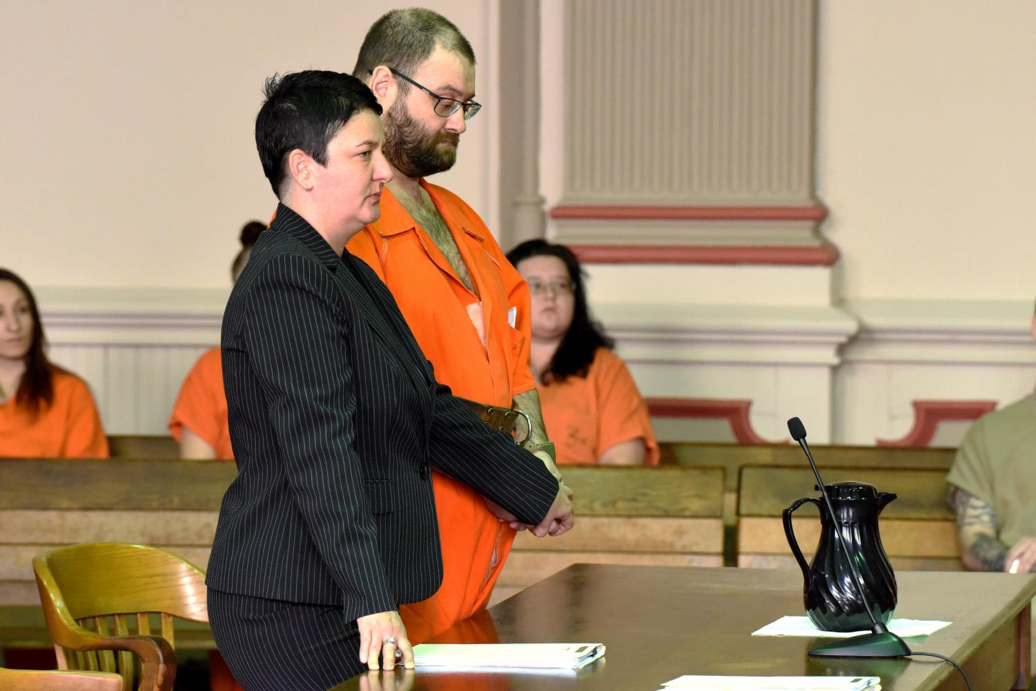 Matthew Stickdorn listens to Judge Kelly Cottrill sentence him on multiple charges as Stickdorn's defense attorney Nicole Churchill extends a comforting hand to him.