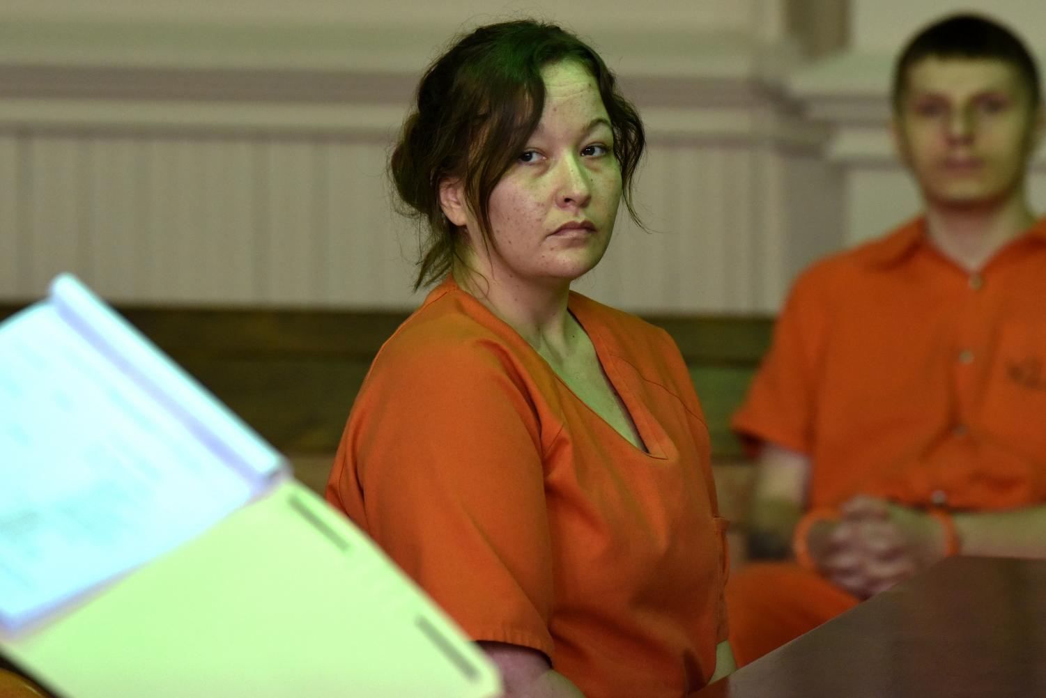 Jessica Eblin watches her defense attorney as he approaches the state's side of the courtroom to utter a clarification during her plea hearing.