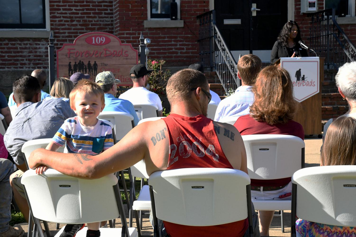 A boy becomes fascinated with the back of the crowd seated on the ForeverDads' lawn as the Executive Director of the Commission on Fatherhood, Kimberly Dent, speaks.
