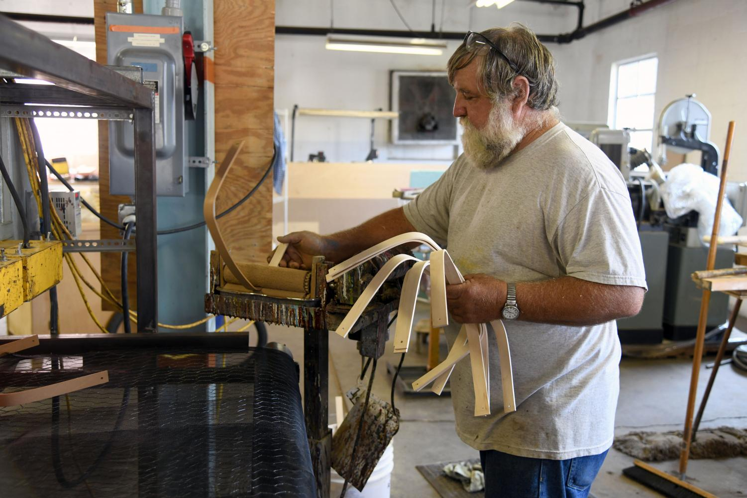 Former long-time Longaberger employee Randy Beach stains handles to be used on Dresden & Company's new line of baskets.