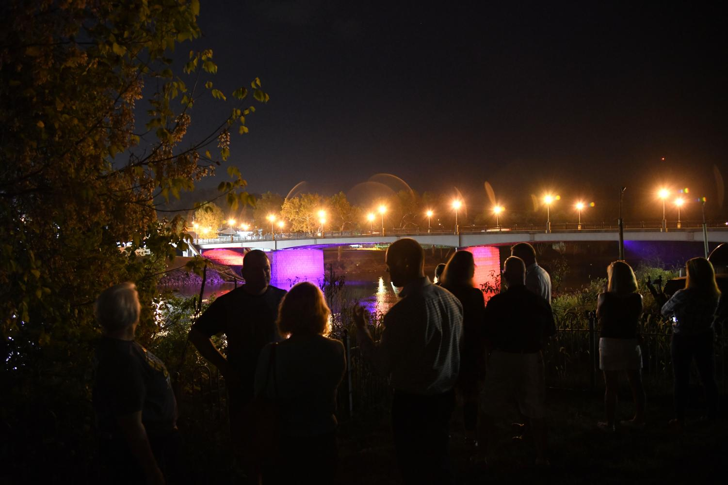 Community members involved in making the bridge lighting possible gathered at Restoration Park Tuesday evening to view the lights.