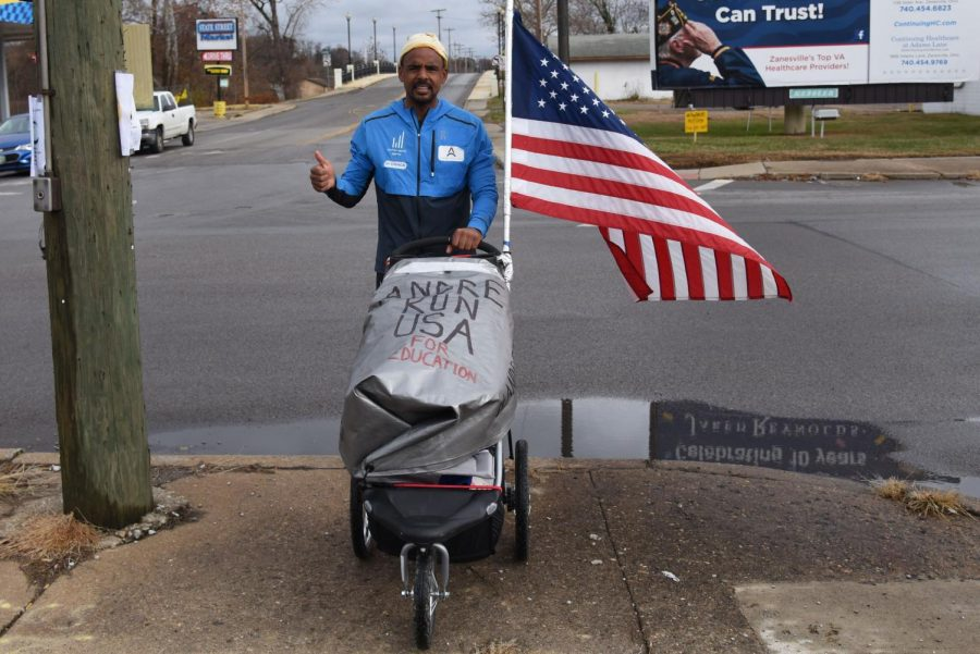 Andre+Belibi+Eloumou+takes+a+break+from+running+along+W.+Main+Street+in+Zanesville+to+share+his+cause.+He+arrived+in+Zanesville+Thursday+night+after+running+25+miles+from+Cambridge.+
