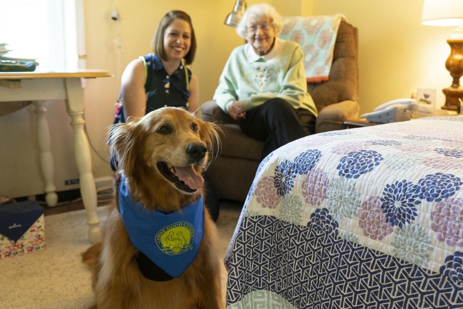 Maggie the Therapy Dog looks for a treat while visiting Helen Purcell. Her owner, Lisa Marshall, and resident Henrietta Hurst watch in the background.