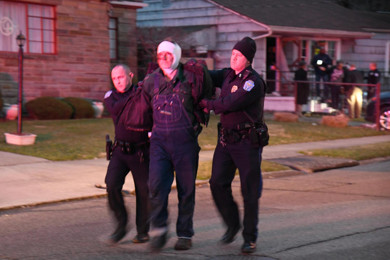 Officers escort Michael Perdue to a police cruiser in handcuffs.