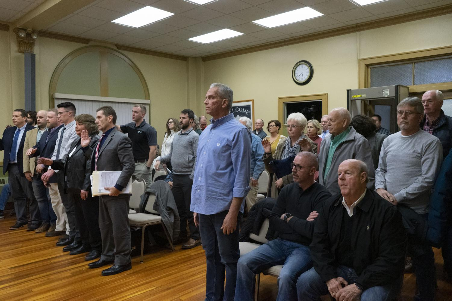 People in the audience of the Zanesville Board of Zoning Appeals who wished to speak during the meeting stand to take an oath.