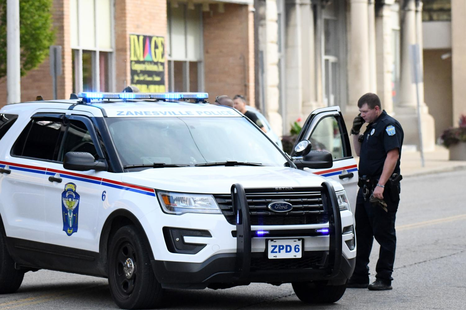 Officer Charles Lewis stands outside a patrol vehicle during an incident in Downtown Zanesville in September.