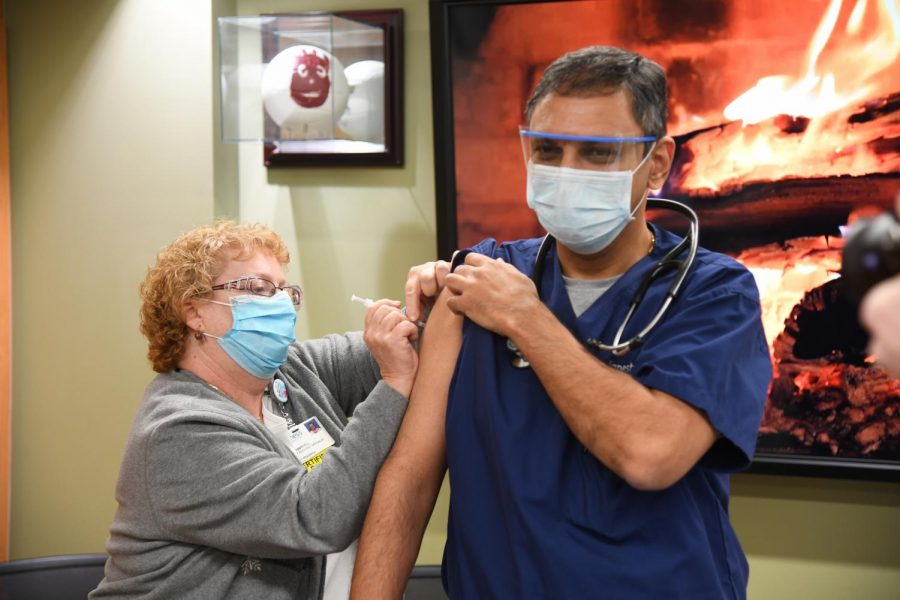 Genesis HealthCare System Pharmacy Research Nurse, Terri Campbell (left) administers the first Pfizer COVID-19 vaccine to Genesis Infectious Diseases Specialist, Dr. Jignesh Modi (right).