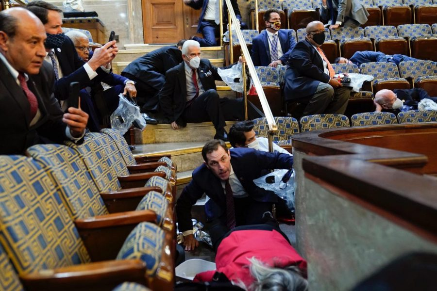 Representative Bill Johnson (center) is seated on stairs inside the chamber of the U.S. House of Representatives while holding a CBRN Escape Hood. Credit: Andrew Harnik @ Associated Press