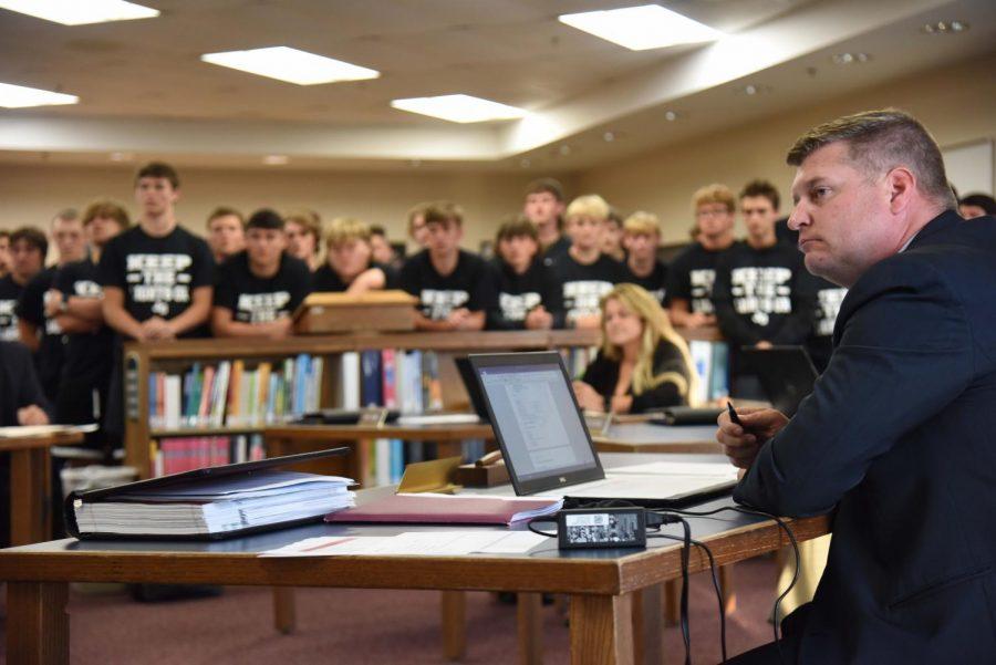 East Muskingum School Board President Matt Abbott listens to student leaders discuss why home football games should remain at East Muskingum.